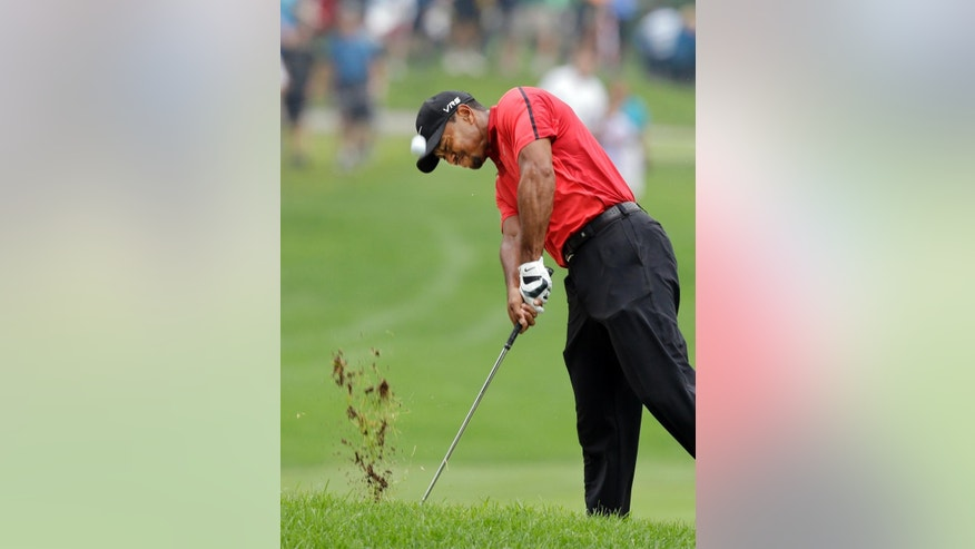 Tiger Woods hits from the lip of a fairway trap on the second hole during the final round of the Bridgestone Invitational golf tournament Sunday, Aug. 3, 2014, at Firestone Country Club in Akron, Ohio. (AP Photo/Mark Duncan)