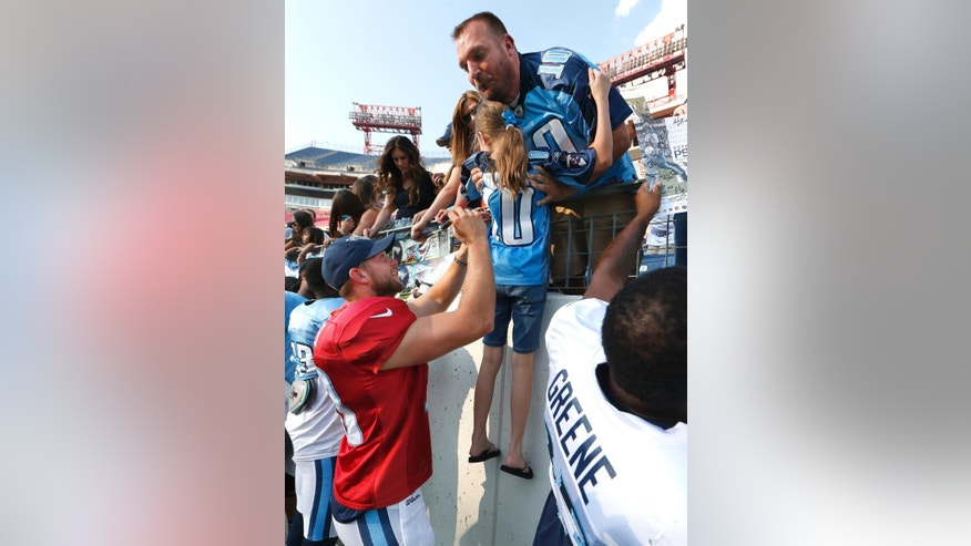 Tennessee Titans quarterback Jake Locker, left, autographs the jersey of a young fan before NFL football training camp practice in LP Field on Saturday, Aug. 2, 2014, in Nashville, Tenn. (AP Photo/Mark Humphrey)