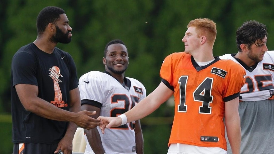 Cincinnati Bengals quarterback Andy Dalton (14) talks with, left to right, tight end Jermaine Gresham, running back Giovani Bernard, and tight end Tyler Eifert during practice at the NFL football team's training camp, Friday, Aug. 1, 2014, in Cincinnati.  (AP Photo/Al Behrman)