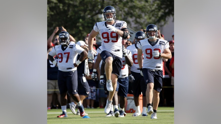 "FILE - In this July 27, 2014 file photo, Houston Texans defensive end J.J. Watt (99) stretches with teammates during an NFL football training camp practice in Houston. Watt knows it's cliche to say ""we're working hard every day"" and he's ""just trying to be a good teammate.""(AP Photo/David J. Phillip, File)"