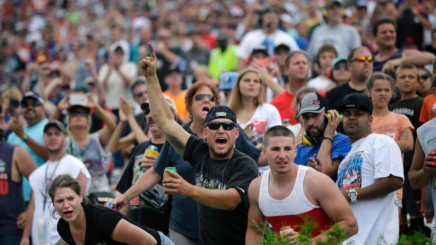 Fans cheer as Dale Earnhardt Jr. leads late in the NASCAR Sprint Cup Series auto race at Pocono Raceway, Sunday, Aug. 3, 2014, Long Pond, Pa. Earnhardt  won the race. (AP Photo/Mel Evans)
