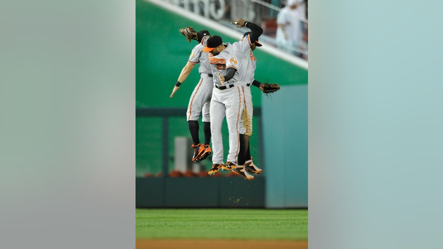Baltimore Orioles' Nick Markakis, center, Adam Jones, right, and David Lough, left, celebrate  the 7-3 win over the Washington Nationals in a baseball game, Monday, Aug. 4, 2014, in Washington. (AP Photo/Nick Wass)