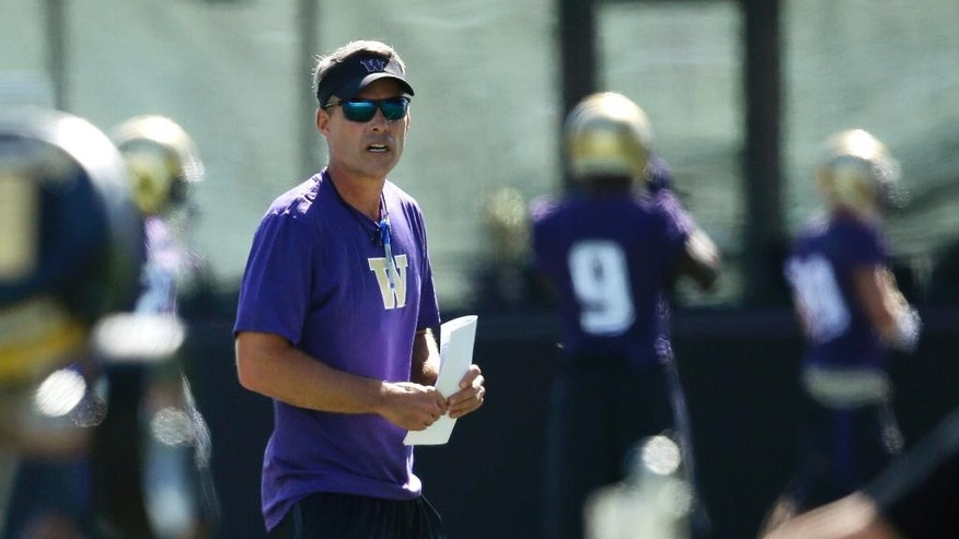 New Washington head coach Chris Petersen walks on the field during the first session of NCAA college football practice before the upcoming fall season, Monday, Aug. 4, 2014, in Seattle. (AP Photo/Ted S. Warren)