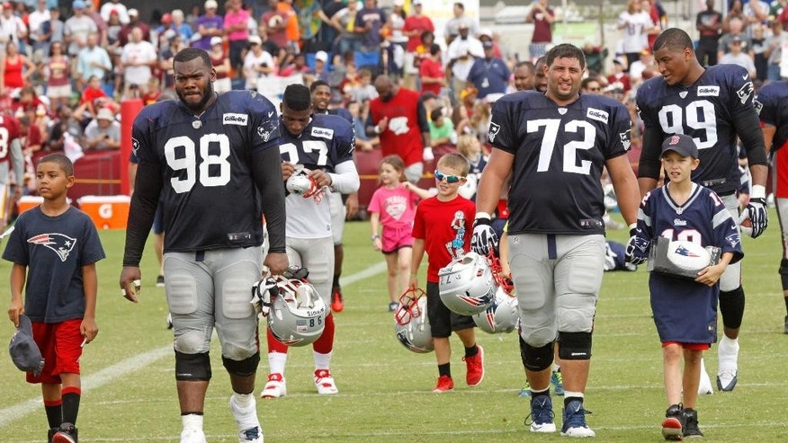 New England Patriot's Marcus Forston (98) and Joe Vellano (72) walk off the field with kids picked at random after a joint team practice with the Washington Redskins in Richmond, Va., Monday, Aug. 4, 2014. (AP Photo/Jay Paul)