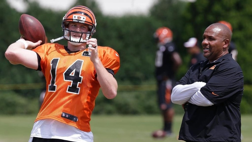 Cincinnati Bengals offensive coordinator Hue Jackson watches quarterback Andy Dalton (14) during practice at the NFL football team's training camp, Thursday, July 31, 2014, in Cincinnati.  (AP Photo/Al Behrman)