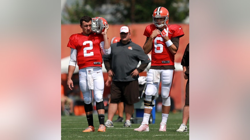 Cleveland Browns quarterbacks Johnny Manziel (2) and Brian Hoyer watch teammates at the NFL football team's training camp in Berea, Ohio, Thursday, July 31, 2014. (AP Photo/Aaron Josefczyk)