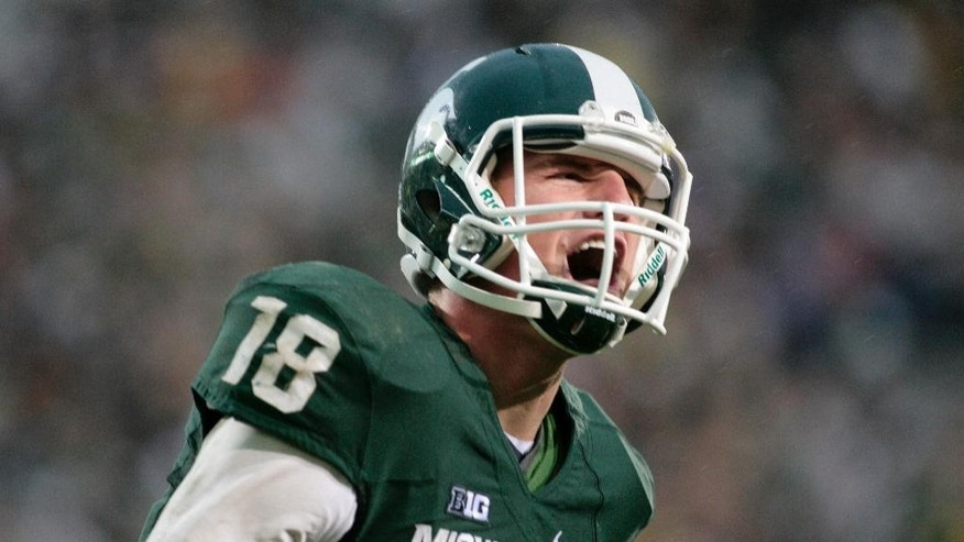 FILE - In this Nov. 2, 2013, file photo,  Michigan State quarterback Connor Cook yells in celebration after scoring a touchdown against Michigan during an NCAA college football game, in East Lansing, Mich. Cook finished the 2013 season strong, throwing for 304 yards and three touchdowns against Ohio State in the Big Ten championship game and for a career-high 332 yards and two TDs against Stanford while being named Offensive MVP of the Rose Bowl. (AP Photo/Al Goldis)