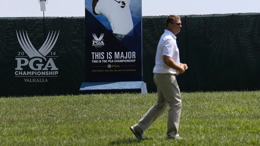 A man walks past a photo of golfer Tiger Woods at the PGA Championship golf tournament at Valhalla Golf Club Monday, Aug. 4, 2014, in Louisville, Ky. Whether Woods will play in the tournament, which is set to begin on Thursday, is unclear after he suffered a setback Sunday when he was stricken with back pain and withdrew after eight holes from the Bridgestone Invitational. (AP Photo/Jeff Roberson)