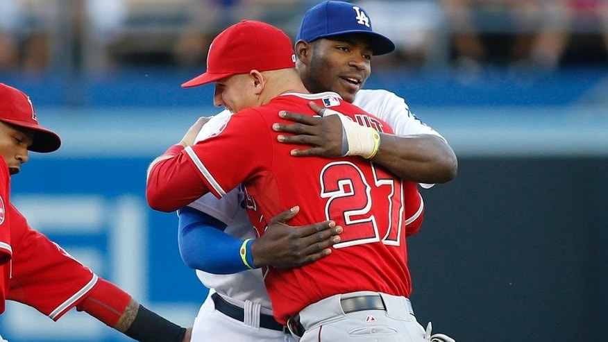 Los Angeles Angels' Mike Trout, left, and Los Angeles Dodgers' Yasiel Puig embrace before a baseball game, Monday, August 4, 2014, in Los Angeles. (AP Photo/Danny Moloshok)