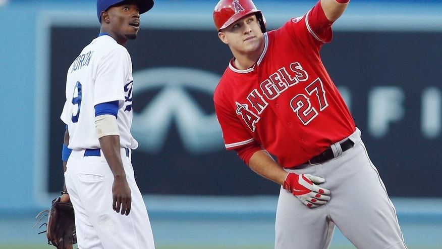 Los Angeles Angels' Mike Trout, right, points something out to Los Angeles Dodgers second baseman Dee Gordon, left, after hitting a double to score Kole Calhoun during the first inning of a baseball game, Monday, August 4, 2014, in Los Angeles. (AP Photo/Danny Moloshok)