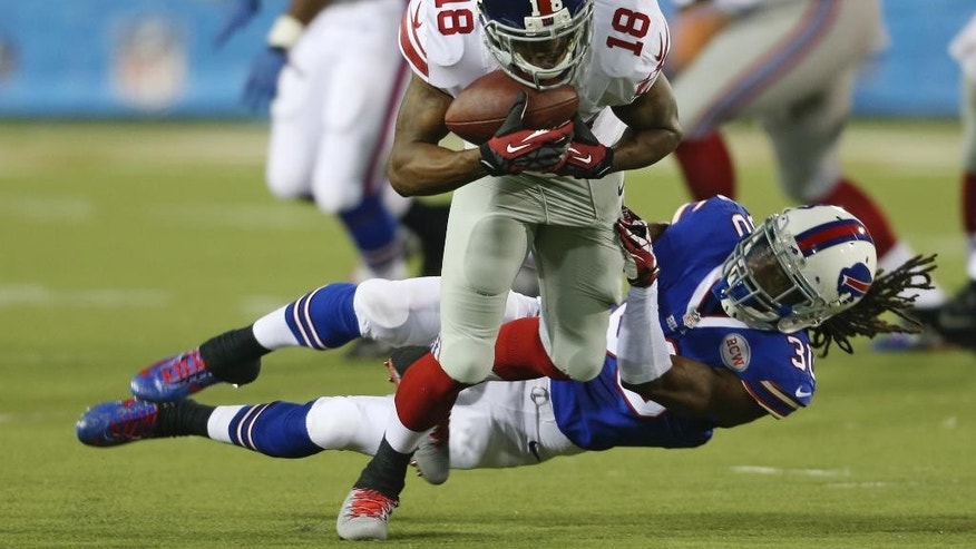New York Giants wide receiver Marcus Harris (18) tries to break away from Buffalo Bills defensive back Mario Butler (30) after Harris caught a pass in the second quarter at the Pro Football Hall of Fame exhibition NFL football game Sunday, Aug. 3, 2014, in Canton, Ohio. (AP Photo/Ron Schwane)