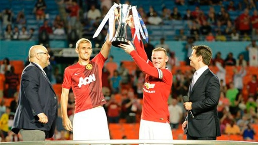 IMAGE DISTRIBUTED FOR GUINNESS INTERNATIONAL CHAMPIONS CUP - Manchester United's Darren Fletcher, left and Wayne Rooney hold the 2014 Guinness International Champions Cup after they defeated Liverpool, on Monday, August 4, 2014  in Miami Gardens, FL.  (Doug Murray/AP Images for Guinness International Champions Cup)