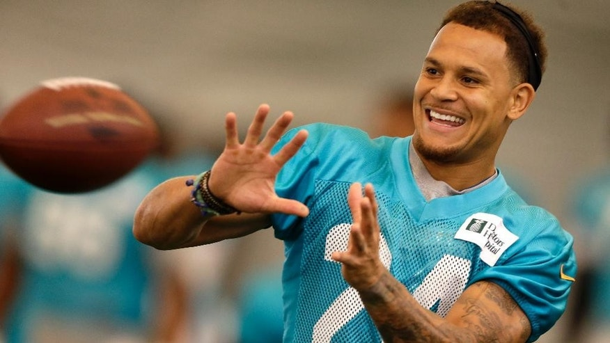 Miami Dolphins cornerback Cortland Finnegan (24) smiles as he prepares to catch a pass during NFL football training camp in Davie, Fla., Monday,Aug. 4, 2014. (AP Photo/Alan Diaz)
