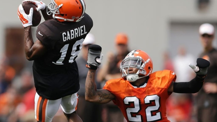 Cleveland Browns wide receiver Taylor Gabriel, left, catches a pass as defensive back Buster Skrine watches during practice at the NFL football team's training camp Tuesday, Aug. 5, 2014, in Berea, Ohio. Skrine is wearing small boxing gloves to keep him from grabbing jersey's of wide receivers. (AP Photo/Tony Dejak)