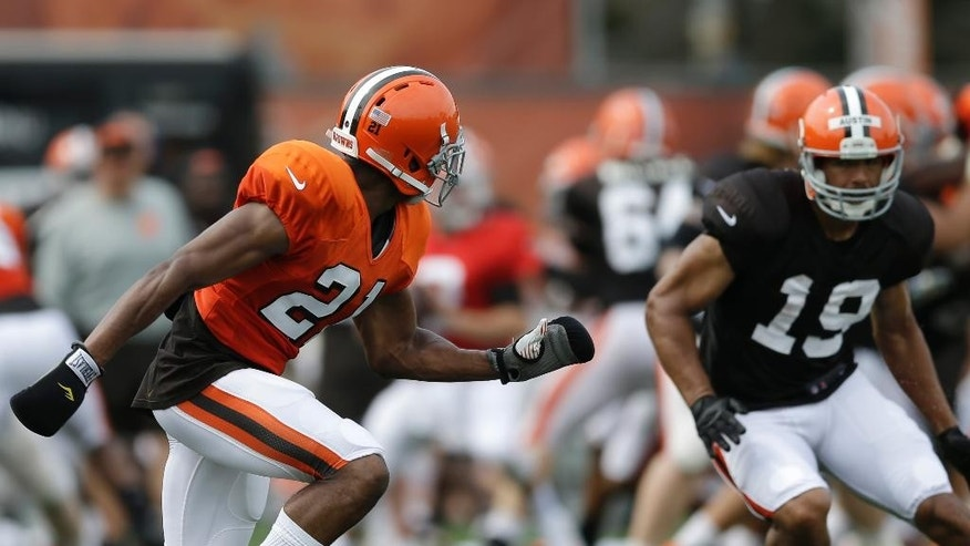 Cleveland Browns cornerback Justin Gilbert, left, defends against wide receiver Miles Austin during practice at the NFL football team's training camp Tuesday, Aug. 5, 2014, in Berea, Ohio. Gilbert is wearing small boxing gloves to keep him from grabbing jersey's of wide receivers.(AP Photo/Tony Dejak)