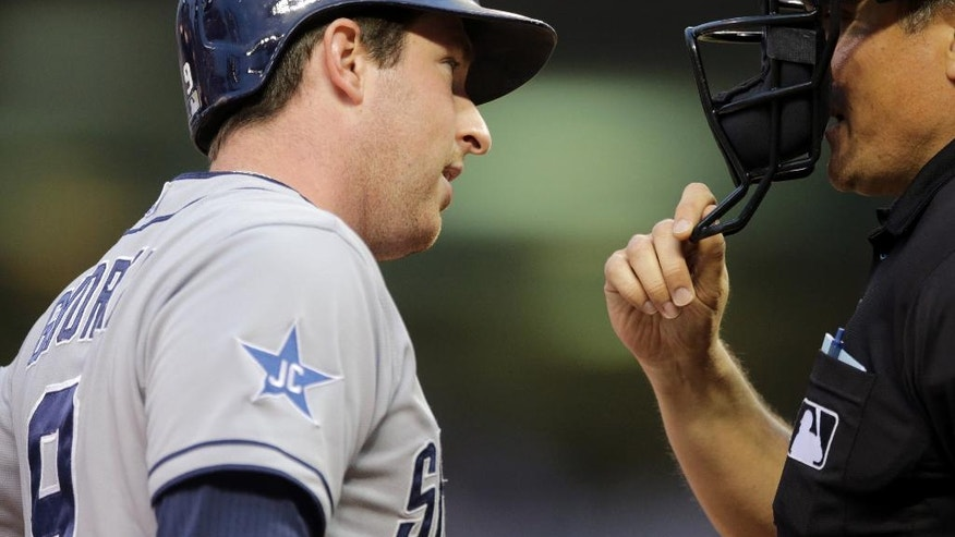 San Diego Padres' Jedd Gyorko, left, questions plate umpire Mike DiMuro after he was called out on strikes in the fourth inning of a baseball game against the Minnesota Twins, Tuesday, Aug. 5, 2014, in Minneapolis. (AP Photo/Jim Mone)