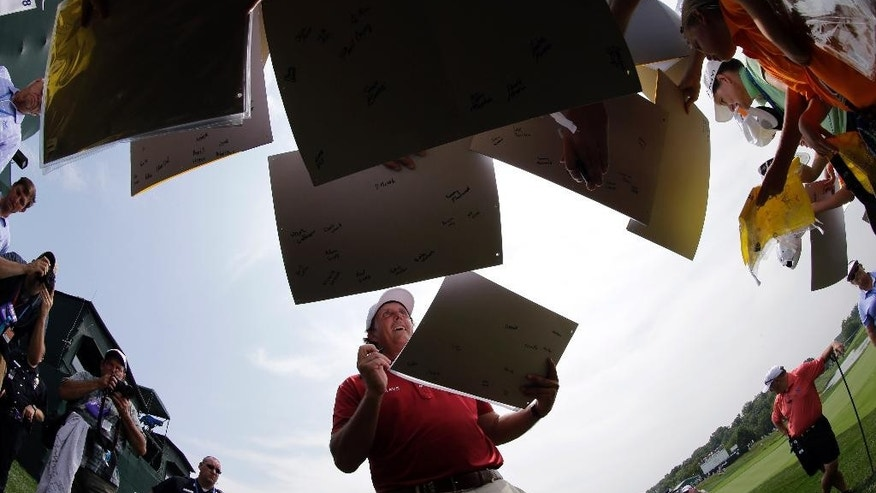 Phil Mickelson signs autographs after a practice round for the PGA Championship golf tournament at Valhalla Golf Club on Tuesday, Aug. 5, 2014, in Louisville, Ky. The tournament is set to begin on Thursday. (AP Photo/David J. Phillip)