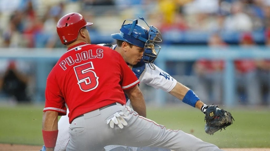 Los Angeles Dodgers' catcher A.J. Ellis tags out Los Angeles Angels' Albert Pujols at home plate during the first nning of a baseball game, Monday, August 4, 2014, in Los Angeles. (AP Photo/Danny Moloshok)