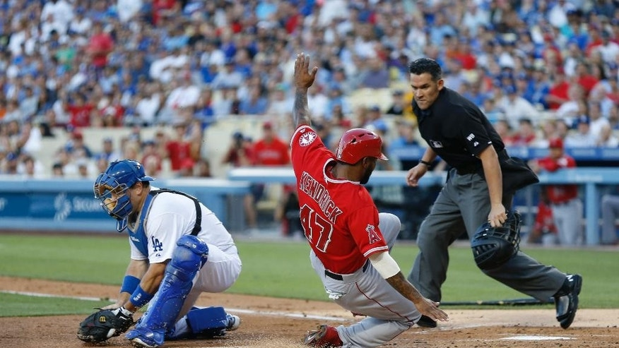 Los Angeles Angels' Howie Kendrick, center, scores past Los Angeles Dodgers catcher A.J. Ellis, left, as home plate umpire Manny Gonzalez, right, looks to make the call on a single by Angels' David Freese during the first inning of a baseball game, Monday, August 4, 2014, in Los Angeles. (AP Photo/Danny Moloshok)