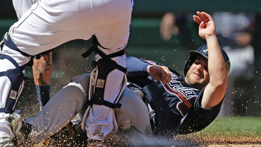 Atlanta Braves' Tommy La Stella is tagged out at home after following in two teammates that scored ahead of him on a double by Freddie Freeman against the Seattle Mariners in the third inning of a baseball game Wednesday, Aug. 6, 2014, in Seattle. (AP Photo/Elaine Thompson)