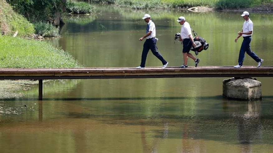 Tiger Woods, left, and Steve Stricker, right cross the foot bridge on the second hole during a practice round for the PGA Championship golf tournament at Valhalla Golf Club on Wednesday, Aug. 6, 2014, in Louisville, Ky. The tournament is set to begin on Thursday. (AP Photo/David J. Phillip)