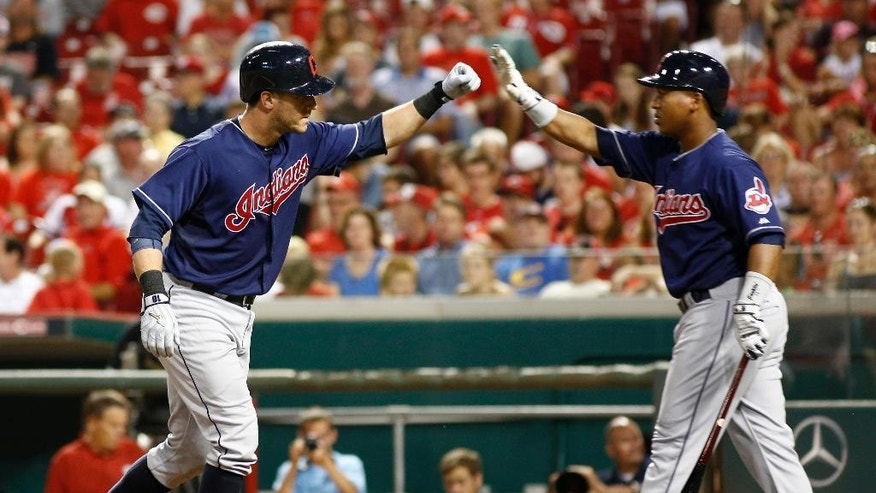 Cleveland Indians' Yan Gomes, left, is congratulated by Jose Ramirez, right, after Gomes hit a solo home run off Cincinnati Reds starting pitcher Mat Latos in the eighth inning of a baseball game, Wednesday, Aug. 6, 2014, in Cincinnati. The Reds won 8-3. (AP Photo/David Kohl)