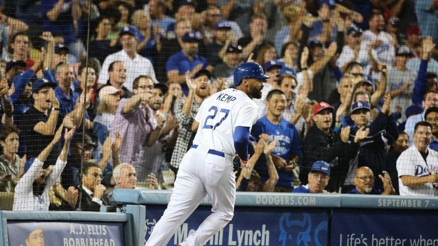 Los Angeles Dodgers' Matt Kemp runs toward the dugout after scoring on a sacrifice fly by Scott Van Slyke during the sixth inning of a baseball game against the Los Angeles Angels on Tuesday, Aug. 5, 2014, in Los Angeles. (AP Photo/Jae C. Hong)