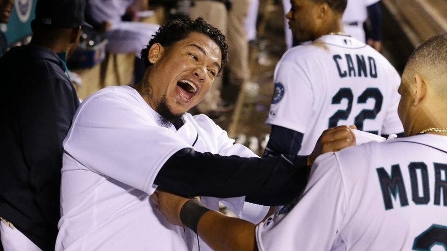 Seattle Mariners starting pitcher Felix Hernandez, left, lets out a yell and playfully grabs teammate Kendrys Morales' jersey after coming out of the baseball game after throwing eight innings against the Atlanta Braves on Tuesday, Aug. 5, 2014, in Seattle. (AP Photo/Elaine Thompson)