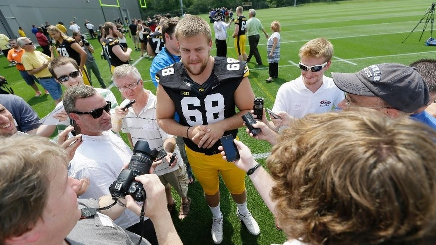 Iowa offensive linesman Brandon Scherff (68) speaks to the media during Iowa's annual college football media day, Monday, Aug. 4, 2014, in Iowa City, Iowa. (AP Photo/Charlie Neibergall)