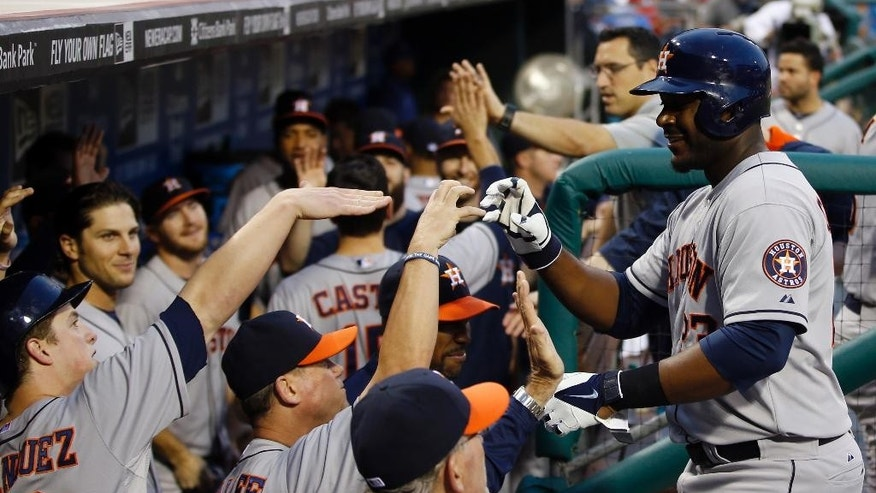 Houston Astros' Chris Carter, right, celebrates with coaches and teammates after hitting a two-run home run off Philadelphia Phillies starting pitcher Sean O'Sullivan during the third inning of an interleague baseball game, Thursday, Aug. 7, 2014, in Philadelphia. (AP Photo/Matt Slocum)