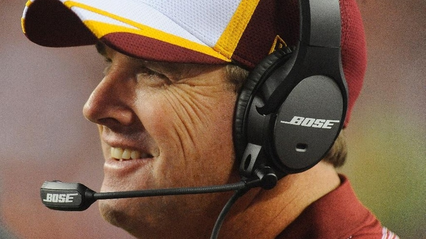 Washington Redskins coach Jay Gruden smiles as he watches during the second half of the Redskins' NFL football preseason game against the New England Patriots in Landover, Md., Thursday, Aug. 7, 2014. (AP Photo/Richard Lipski)