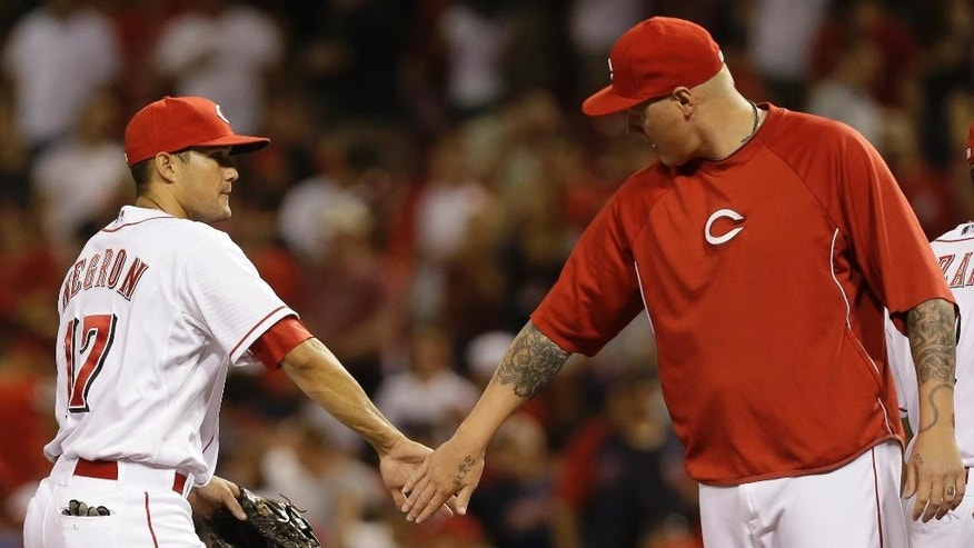 Cincinnati Reds' Kris Negron (17) is congratulated by Mat Latos after the Reds defeated the Cleveland Indians 4-0 in a baseball game, Thursday, Aug. 7, 2014, in Cincinnati. (AP Photo/Al Behrman)