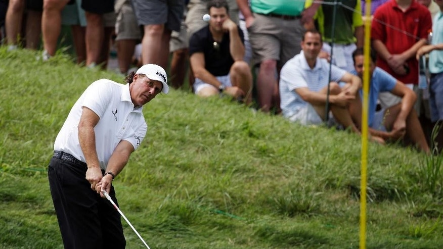 Phil Mickelson hits a chip on the fifth hole during the first round of the PGA Championship golf tournament at Valhalla Golf Club on Thursday, Aug. 7, 2014, in Louisville, Ky. (AP Photo/John Locher)
