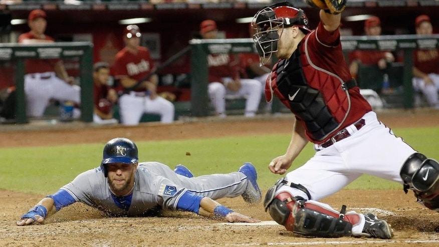 Kansas City Royals' Alex Gordon, left, touches home plate to score a run as Arizona Diamondbacks' Miguel Montero, right, catches a late throw during the third inning of a baseball game on Wednesday, Aug. 6, 2014, in Phoenix. (AP Photo/Ross D. Franklin)
