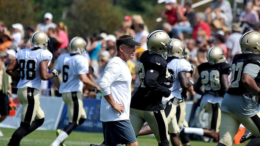New Orleans Saints head coach Sean Payton walks on the field during the teams NFL football training camp in White Sulphur Springs, W.Va., Tuesday, Aug. 5, 2014. (AP Photo/Chris Tilley)