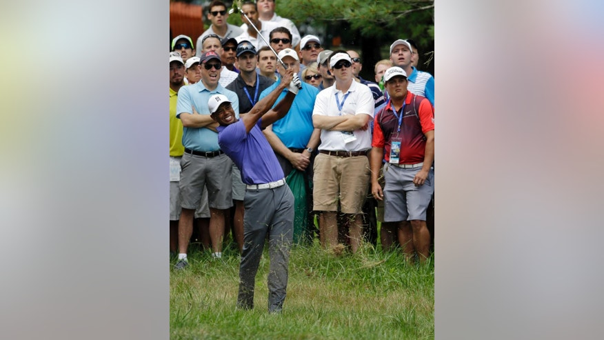 Tiger Woods hits from rough on the first2 hole during the first round of the PGA Championship golf tournament at Valhalla Golf Club on Thursday, Aug. 7, 2014, in Louisville, Ky. (AP Photo/John Locher)