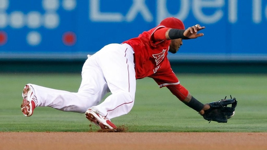 Los Angeles Angels shortstop Erick Aybar does not reach a ground ball hit for a single by Los Angeles Dodgers' Yasiel Puig in the first inning of a baseball game Thursday, Aug. 7, 2014, in Anaheim, Calif. (AP Photo/Alex Gallardo)
