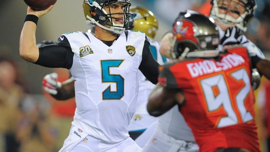 Jacksonville Jaguars quarterback Blake Bortles (5) throws a pass as he is pressured by Tampa Bay Buccaneers defensive end William Gholston (92) during the first half of an NFL preseason football game in Jacksonville, Fla., Friday, Aug. 8, 2014. (AP Photo/Stephen B. Morton)