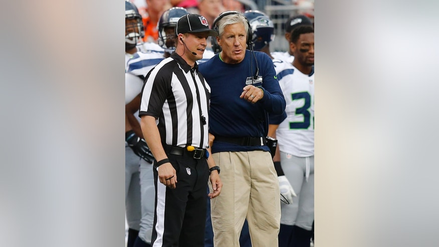 Seattle Seahawks head coach Pete Carroll talks with the referee during the first half of an NFL preseason football game, Thursday, Aug. 7, 2014, in Denver. (AP Photo/Jack Dempsey)
