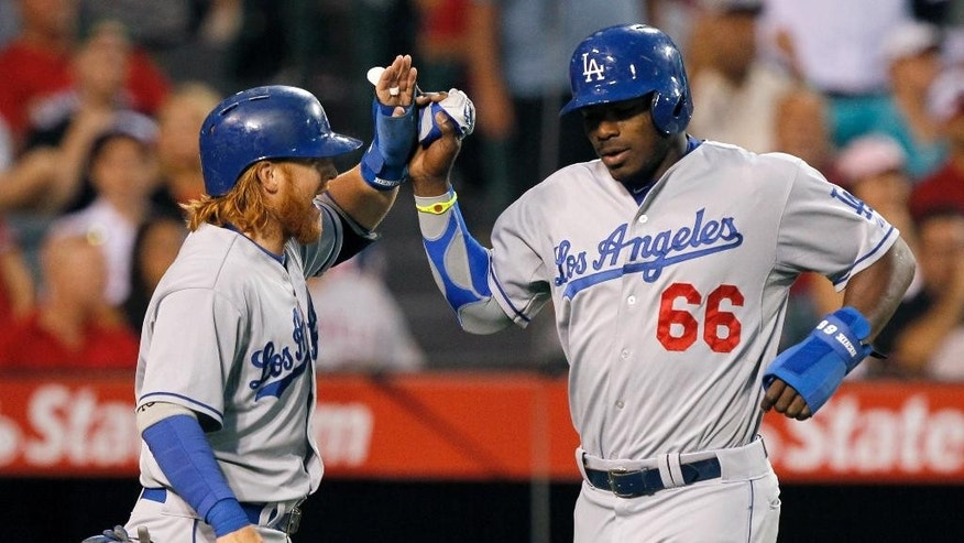 Los Angeles Dodgers' Justin Turner, left, congratulates Yasiel Puig after they scored on a single by Hanley Ramirez in the third inning of a baseball game against the Los Angeles Angels on Thursday, Aug. 7, 2014, in Anaheim, Calif. (AP Photo/Alex Gallardo)
