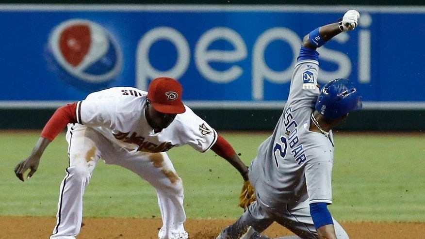Kansas City Royals' Alcides Escobar (2) gets tagged out trying to steal second by Arizona Diamondbacks' Didi Gregorius, left, during the fourth inning of a baseball game Thursday, Aug. 7, 2014, in Phoenix. (AP Photo/Ross D. Franklin)