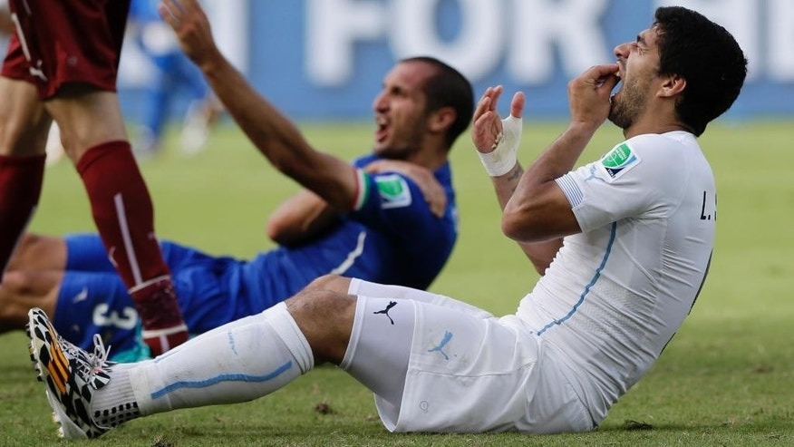 "FILE - In this Tuesday, June 24, 2014 file photo, Uruguay's Luis Suarez holds his teeth after biting Italy's Giorgio Chiellini's shoulder during the group D World Cup soccer match between Italy and Uruguay at the Arena das Dunas in Natal, Brazil.  Luis Suarez should get the verdict next week in his appeal against a four-month ban from football for biting an opponent at the World Cup. The Court of Arbitration for Sport says the decision is ""likely to be rendered some days"" after the closed-doors hearing Friday, Aug. 8, 2014. (AP Photo/Ricardo Mazalan, File)"