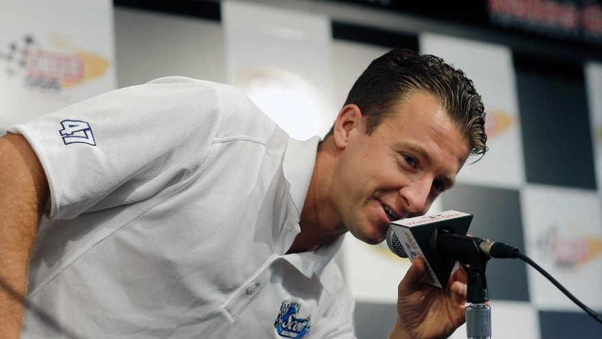 Driver AJ Allmendinger makes a joke as he answers a question before practice session for Sunday's NASCAR Sprint Cup Series auto race at Watkins Glen International, Friday, Aug. 8, 2014, in Watkins Glen N.Y. (AP Photo/Mel Evans)