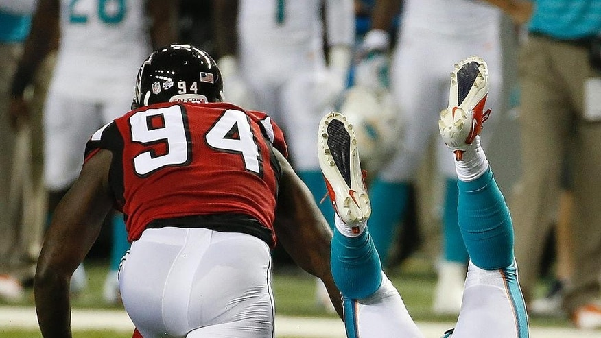 Atlanta Falcons defensive end Jonathan Massaquoi (94) tackles Miami Dolphins running back Damien Williams (5) during the first half of an NFL preseason football game, Friday, Aug. 8, 2014, in Atlanta.  (AP Photo/John Bazemore)