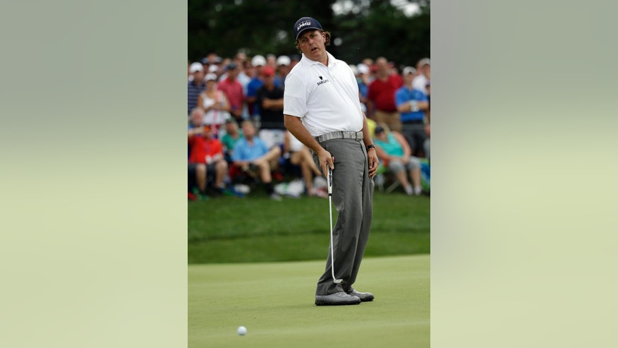 Phil Mickelson reacts to missing his eagle putt on the seventh hole during the third round of the PGA Championship golf tournament at Valhalla Golf Club on Saturday, Aug. 9, 2014, in Louisville, Ky. (AP Photo/David J. Phillip)