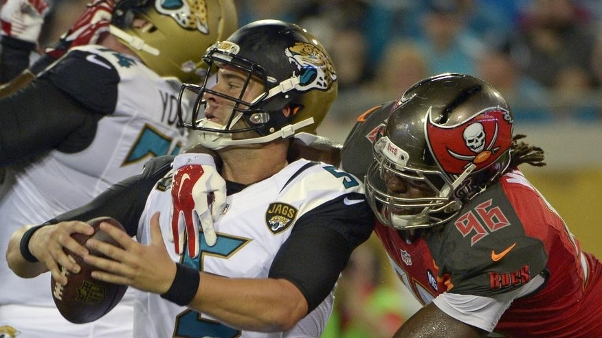 Jacksonville Jaguars quarterback Blake Bortles, left, is sacked by Tampa Bay Buccaneers defensive end Steven Means (96) during the first half of an NFL preseason football game in Jacksonville, Fla., Friday, Aug. 8, 2014. (AP Photo/Phelan M. Ebenhack)