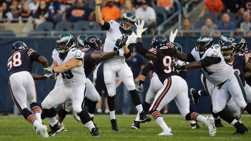 Philadelphia Eagles quarterback Nick Foles (9) throws a pass under pressure by Chicago Bears defensive tackle Jeremiah Ratliff (90) in the first half of an NFL preseason football game Friday, Aug. 8, 2014, in Chicago. (AP Photo/Nam Y. Huh)