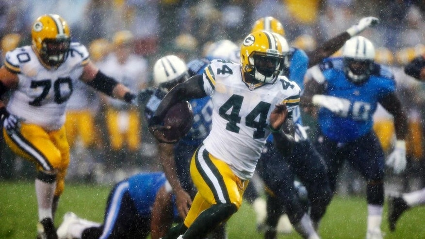 Green Bay Packers running back James Starks (44) runs 20 yards for a touchdown against the Tennessee Titans in the first quarter of a preseason NFL football game in the rain Saturday, Aug. 9, 2014, in Nashville, Tenn. (AP Photo/Wade Payne)