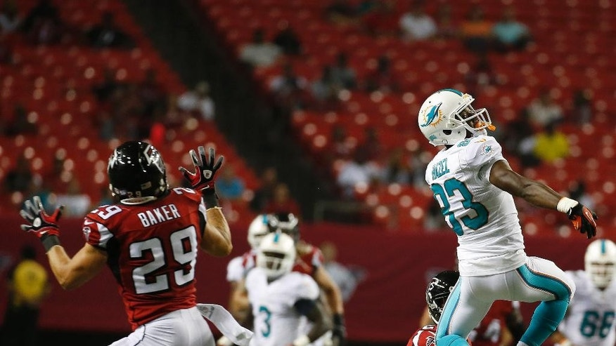 Miami Dolphins wide receiver Matt Hazel (83) misses the ball as Atlanta Falcons defensive back Sean Baker (29) looks on during the second half of an NFL preseason football game, Friday, Aug. 8, 2014, in Atlanta. The Atlanta Falcons won 16-10. (AP Photo/John Bazemore)