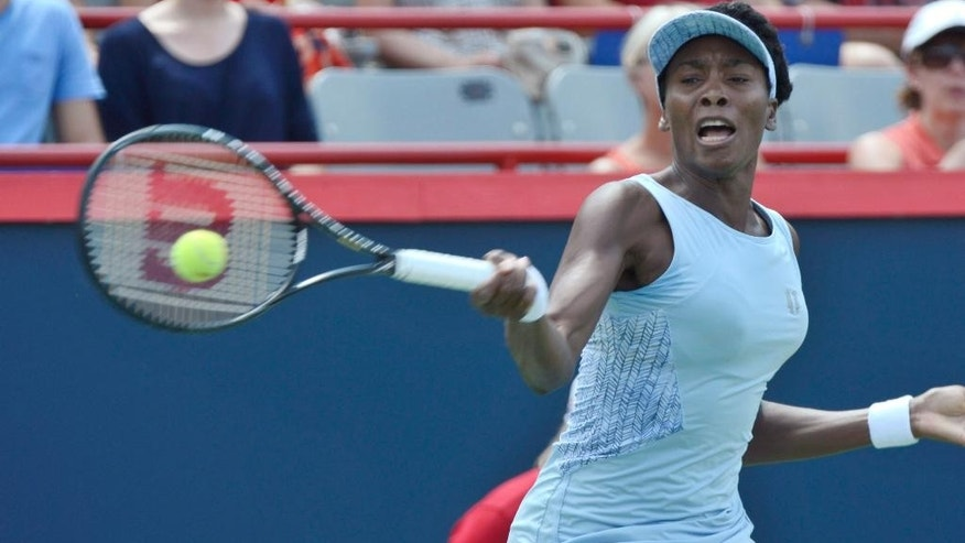 Venus Williams returns to her sister Serena Williams during semifinal play at the Rogers Cup tennis tournament, Saturday, Aug. 9, 2014 in Montreal. (AP Photo/The Canadian Press, Paul Chiasson)